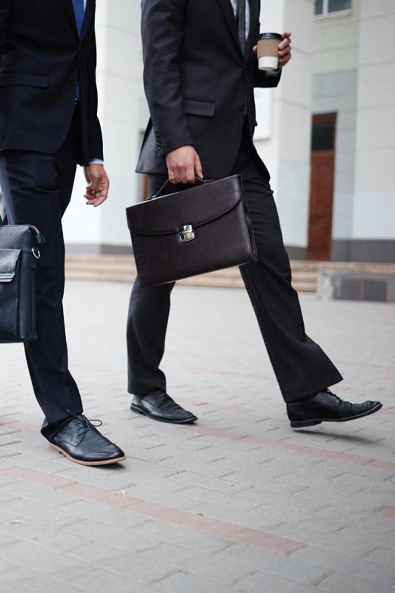 well dressed business people walking down interlock brick street