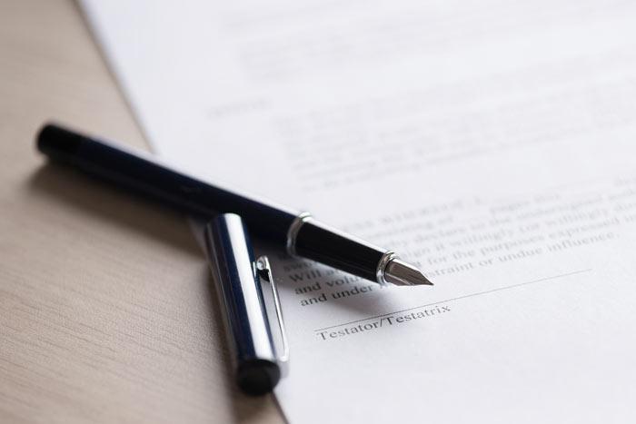 an open fountain pen awaits a signature of a witness
